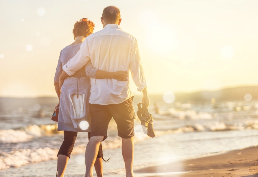 Paar geht im Sonnenuntergang am Strand spazieren.