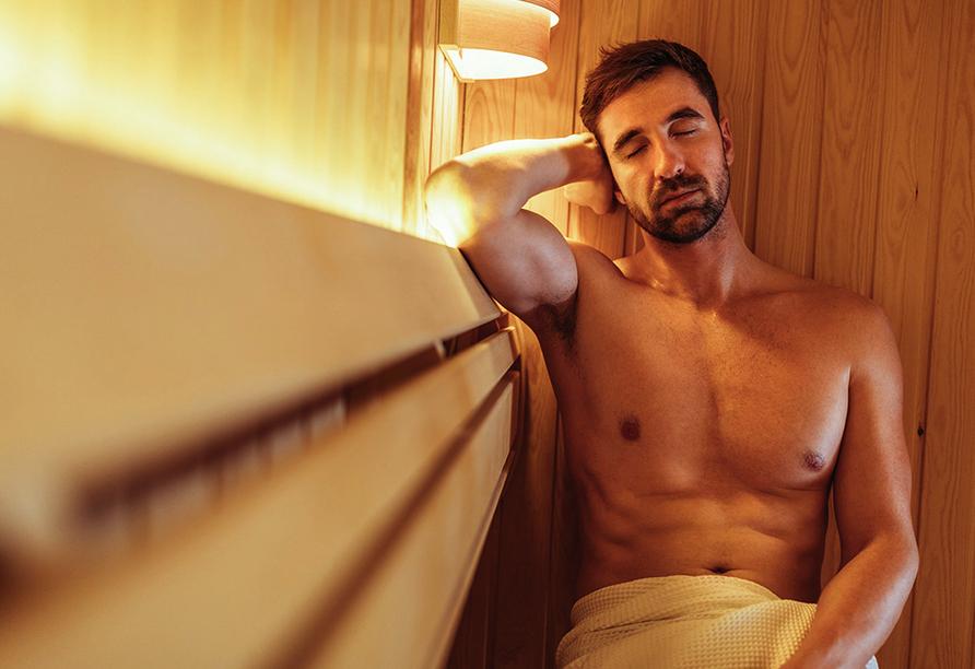 Mann sitzt entspannt und mit geschlossenen Augen in der Sauna