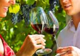Paar trinkt Rotwein zwischen Weinreben.