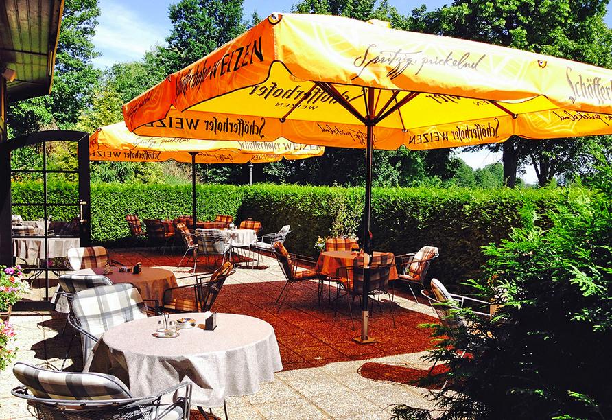 Biergarten mit gelben Sonnenschirmen und Holzstühlen.