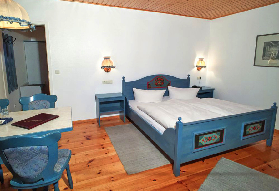 Gemütliches Doppelzimmer mit großem Bett und Dielenboden.