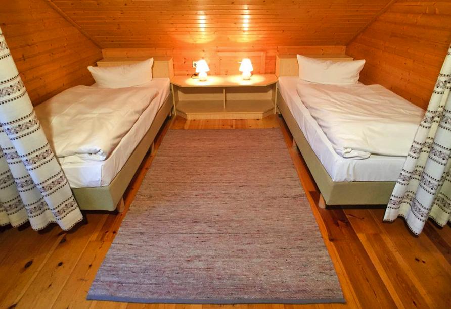 Zwei getrennte Betten im Schlafzimmer mit karierten Vorhängen davor.