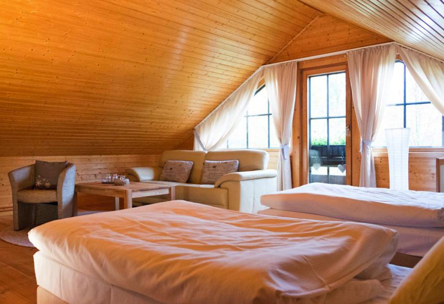 Gemütliches Schlafzimmer mit zwei getrennten Betten vor großem Fenster in Dachschräge.