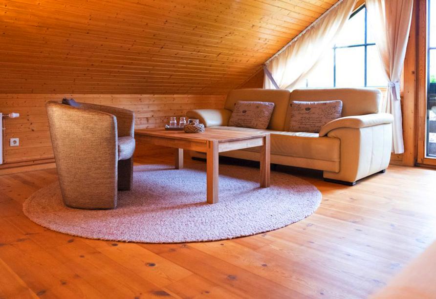 Gemütliche Sitzecke mit Sessel und Sofa vor großem Fenster in Dachschräge.
