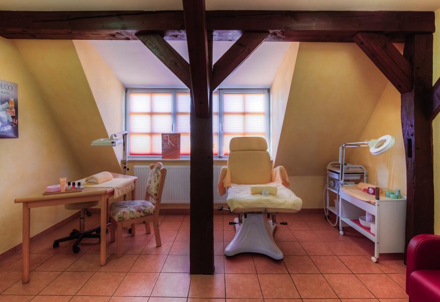 Raum mit Dachschräge und Fachwerkbalken in dem Wellnessanwendungen angeboten werden.