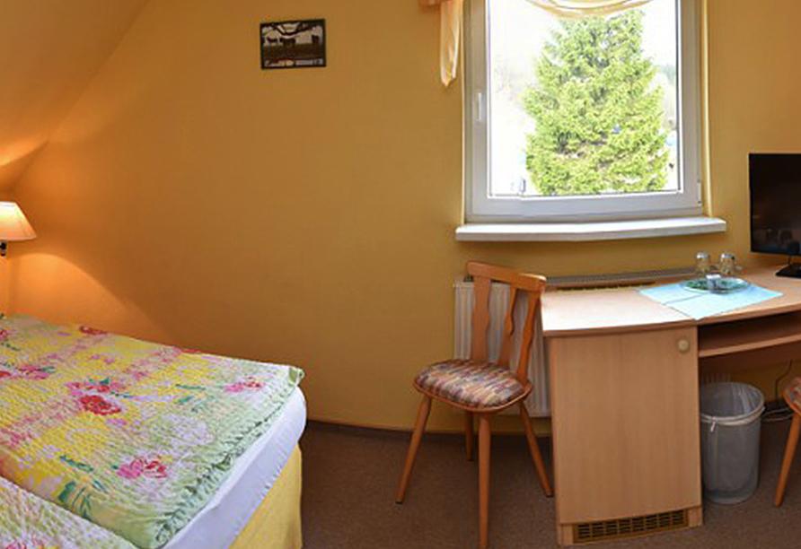 Doppelzimmer mit kleinem Fenster und Schreibtisch.