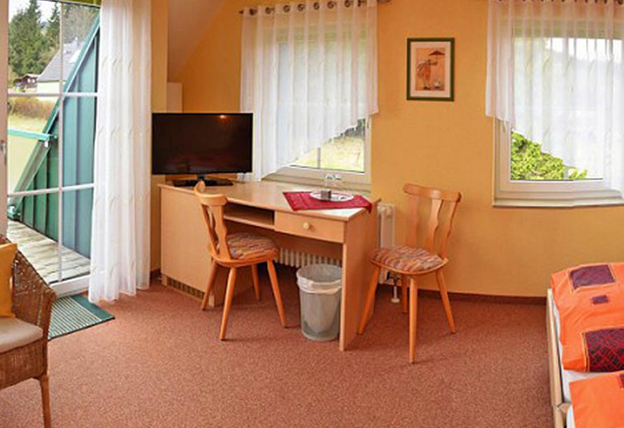 Großes Hotelzimmer mit Schreibtisch und Fernseher.