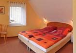 Doppelzimmer mit großem Bett unter Dachschräge.
