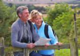 Älteres Paar geht im Wald wandern und schaut auf die Karte.
