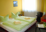 Doppelzimmer mit gelben Wänden und grüner Bettwäsche.
