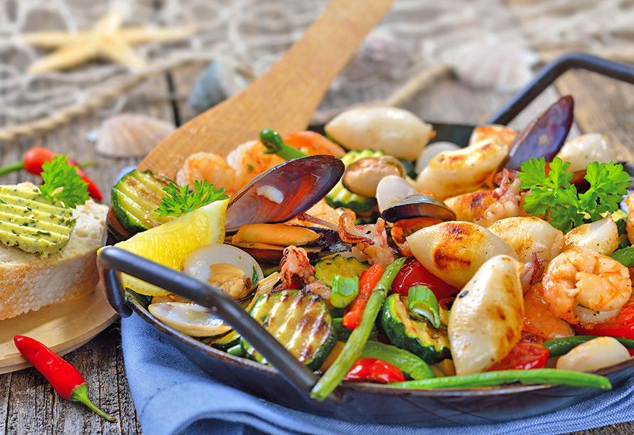 Buntes Pfannengericht mit Gemüse, Gnocchi, Fisch und Muscheln.
