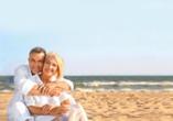 Älteres Paar in weißen Outfits sitz an feinem Sandstrand.