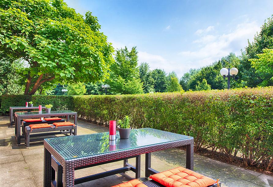 Hotelterrasse mit Sitzgelegenheiten, die von Hecke und Bäumen umgeben ist.