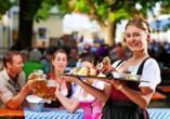 Freuen Sie sich auf eine Brotzeit und ein Maß Bier in einem typisch bayerischen Biergarten.