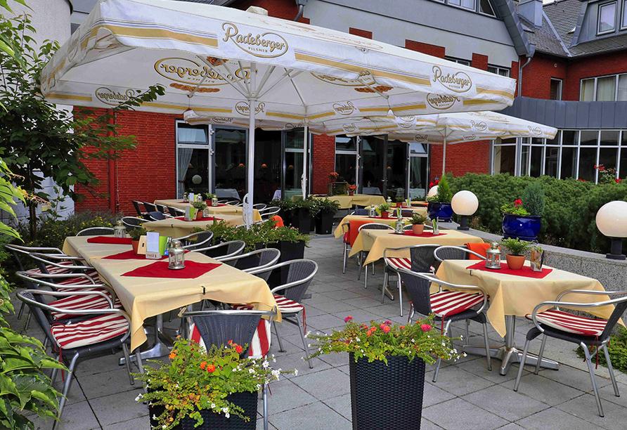 Terrasse mit Sonnenschirmen und gedeckten Tischen.