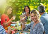 Freunde sitzen im Sommer beim Essen zusammen udn stoßen mit Wein an.