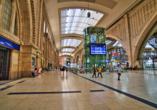 Leipziger Hauptbahnhof und Menschen mit Mundschutzmasken.