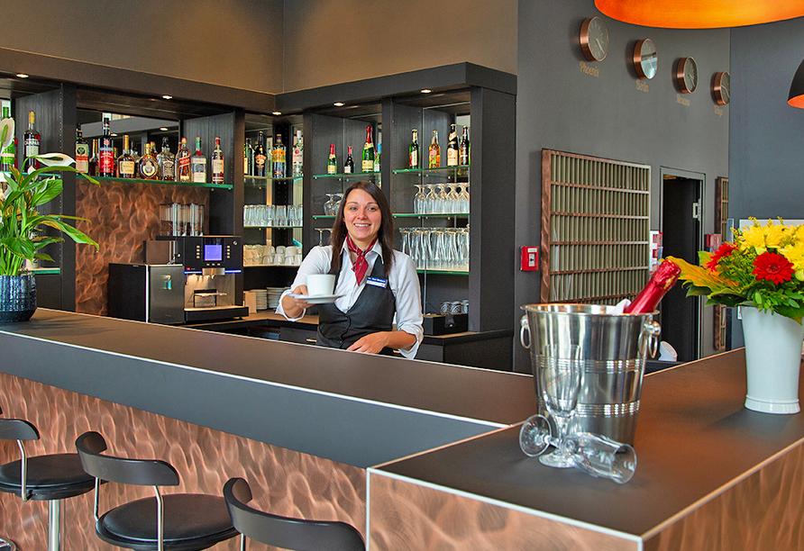 Lächelnde Frau an der Bar hält Kaffeetasse in Richtung Kamera.