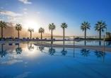 Palmen rund um den Außenpool verbreiten Urlaubsstimmung.