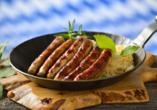 Leckere Rostbratwürste auf Sauerkraut in der Eisenpfanne serviert.